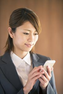 スマートフォンを操作するビジネスウーマンの写真素材 [FYI04557546]