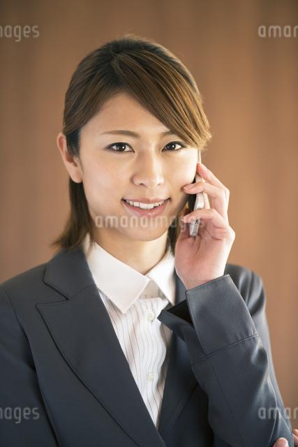 スマートフォンで電話をするビジネスウーマンの写真素材 [FYI04557547]
