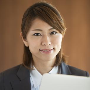 タブレットPCを持ち微笑むビジネスウーマンの写真素材 [FYI04557608]