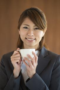 コーヒーカップを持ち微笑むビジネスウーマンの写真素材 [FYI04557609]