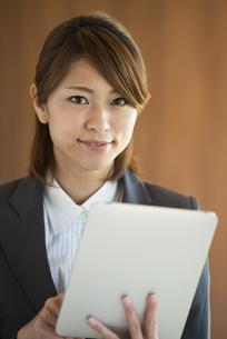 タブレットPCを操作するビジネスウーマンの写真素材 [FYI04557611]