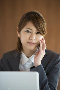 スマートフォンで電話をするビジネスウーマンの写真素材 [FYI04557612]