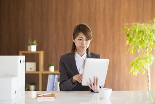 タブレットPCを操作するビジネスウーマンの写真素材 [FYI04557630]