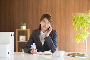 スマートフォンで電話をするビジネスウーマンの写真素材 [FYI04557635]