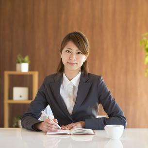 手帳に記入をするビジネスウーマンの写真素材 [FYI04557638]