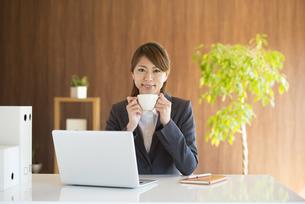 コーヒーカップを持ち微笑むビジネスウーマンの写真素材 [FYI04557648]