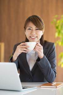 コーヒーカップを持ち微笑むビジネスウーマンの写真素材 [FYI04557654]