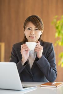 コーヒーカップを持ち微笑むビジネスウーマンの写真素材 [FYI04557658]