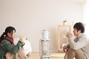 ストーブで温まるカップルの写真素材 [FYI04557684]