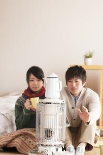 ストーブで温まるカップルの写真素材 [FYI04557692]