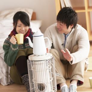 ストーブで温まるカップルの写真素材 [FYI04557693]