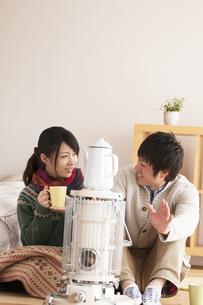 ストーブで温まるカップルの写真素材 [FYI04557695]