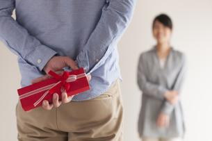 後ろにプレゼントを隠す男性の手元の写真素材 [FYI04557734]