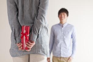 後ろにプレゼントを隠す女性の手元の写真素材 [FYI04557736]
