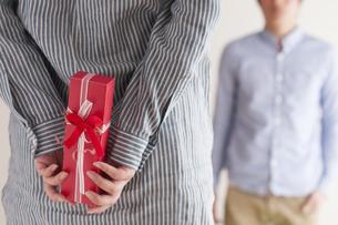 後ろにプレゼントを隠す女性の手元の写真素材 [FYI04557737]