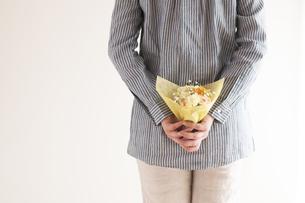 後ろに花束を隠す女性の手元の写真素材 [FYI04557760]