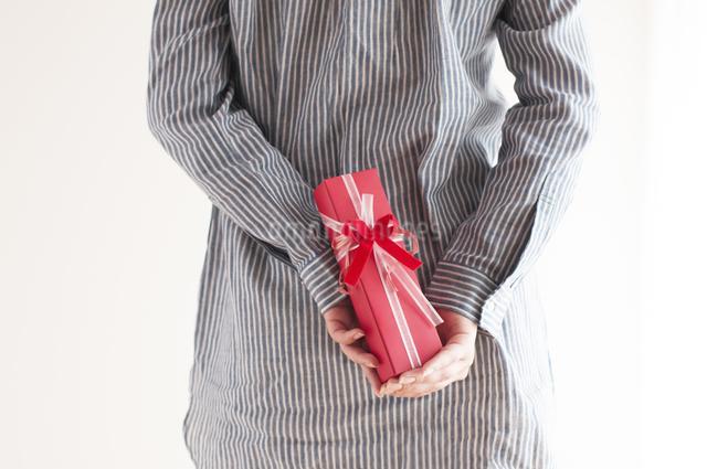 後ろにプレゼントを隠す女性の手元の写真素材 [FYI04557767]