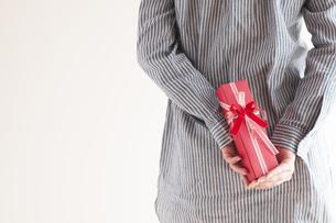 後ろにプレゼントを隠す女性の手元の写真素材 [FYI04557768]
