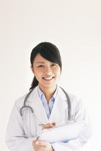 カルテを持つ笑顔の女医の写真素材 [FYI04557789]
