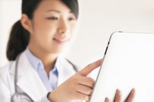 タブレットPCを操作する女医の手元の写真素材 [FYI04557792]