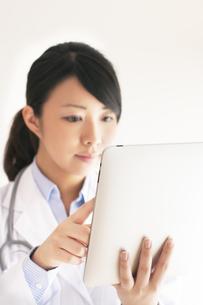 タブレットPCを操作する女医の写真素材 [FYI04557796]