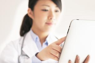 タブレットPCを操作する女医の手元の写真素材 [FYI04557797]