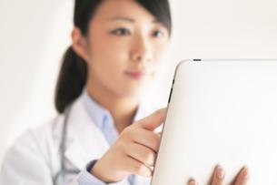 タブレットPCを操作する女医の手元の写真素材 [FYI04557798]