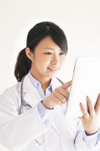 タブレットPCを操作する女医の写真素材 [FYI04557800]
