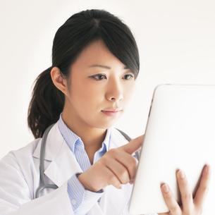 タブレットPCを操作する女医の写真素材 [FYI04557802]