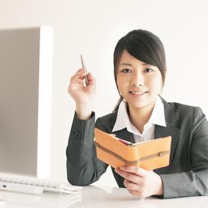スケジュール帳を持ち微笑むビジネスウーマンの写真素材 [FYI04557816]