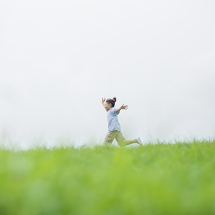 草原を走る女の子の写真素材 [FYI04558014]