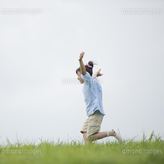 草原を走る女の子の写真素材 [FYI04558021]