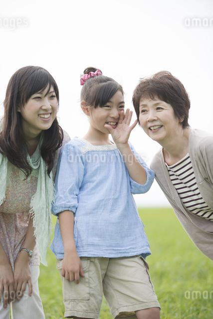 草原で内緒話をする三世代家族の写真素材 [FYI04558023]