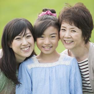 草原で微笑む三世代家族の写真素材 [FYI04558027]