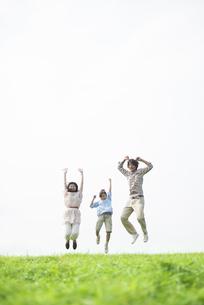 草原でジャンプをする家族の写真素材 [FYI04558042]