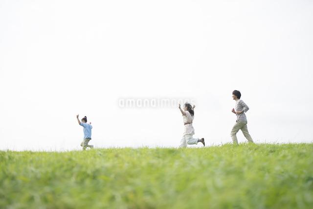 草原を走る家族の写真素材 [FYI04558049]