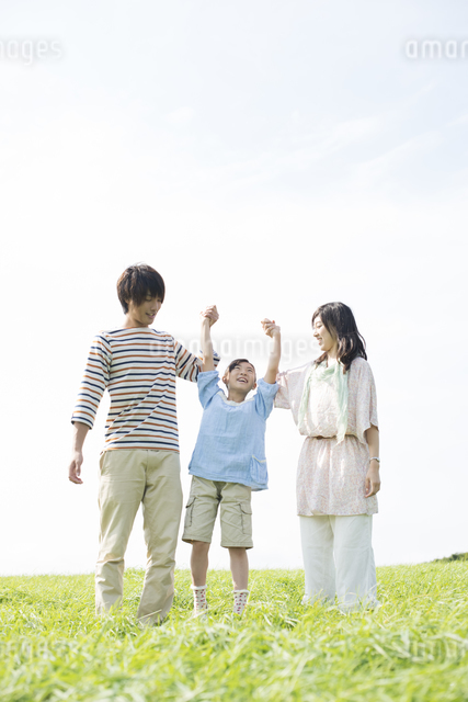 草原で手をつなぐ家族の写真素材 [FYI04558075]