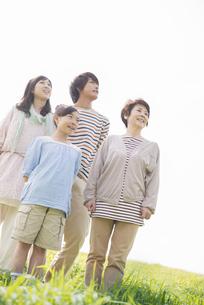 草原で遠くを眺める3世代家族の写真素材 [FYI04558094]