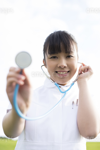 草原で聴診器をあてる看護師の写真素材 [FYI04558125]
