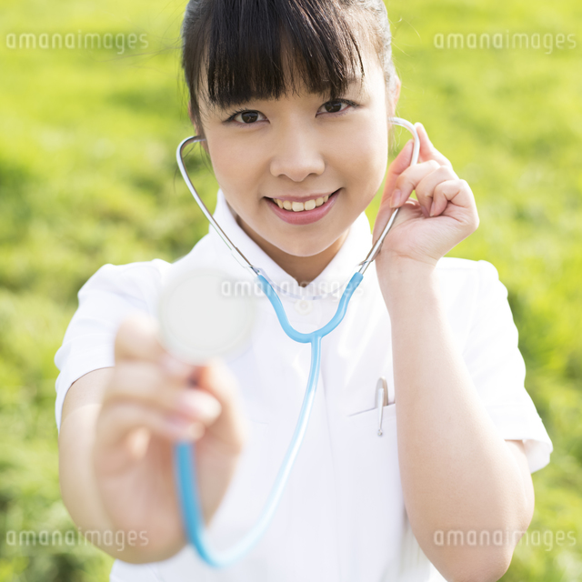 草原で聴診器をあてる看護師の写真素材 [FYI04558127]