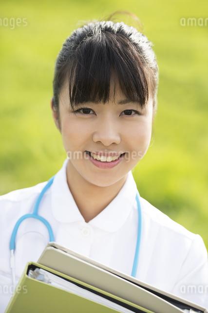 草原でファイルを持つ看護師の写真素材 [FYI04558131]