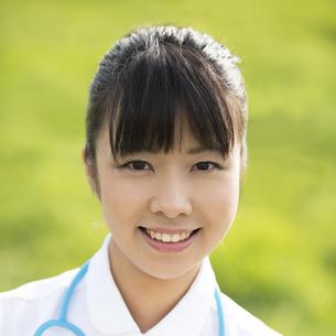 草原で微笑む看護師の写真素材 [FYI04558132]