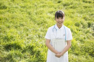 草原でカルテを持つ看護師の写真素材 [FYI04558143]
