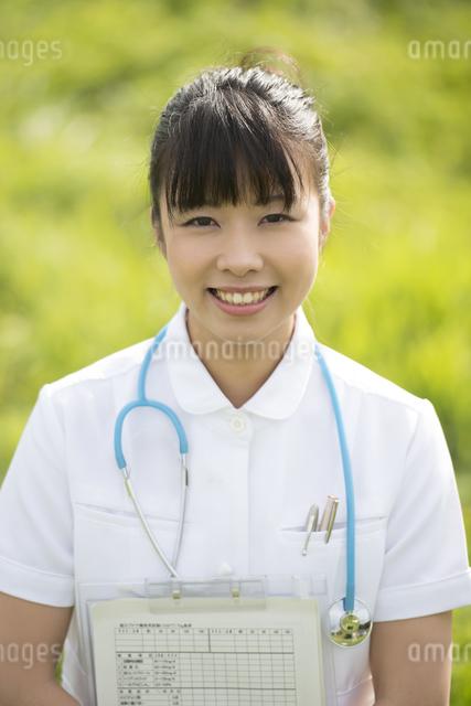 草原でカルテを持つ看護師の写真素材 [FYI04558146]