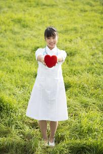 草原でハートを持つ看護師の写真素材 [FYI04558151]