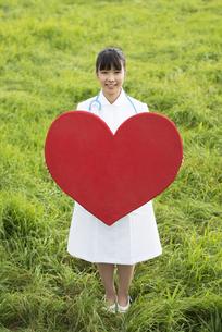 草原でハートを持つ看護師の写真素材 [FYI04558153]