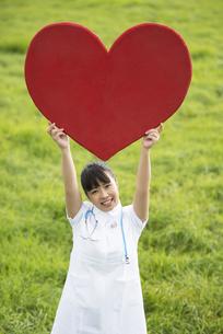 草原でハートを掲げる看護師の写真素材 [FYI04558157]