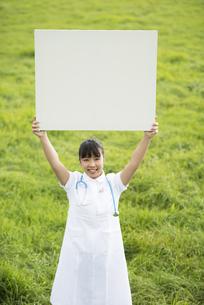 草原でホワイトボードを掲げる看護師の写真素材 [FYI04558158]