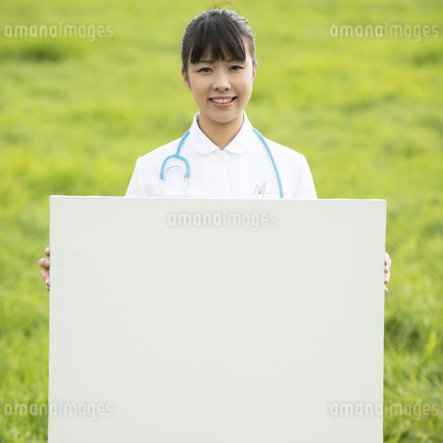 草原でホワイトボードを持つ看護師の写真素材 [FYI04558159]
