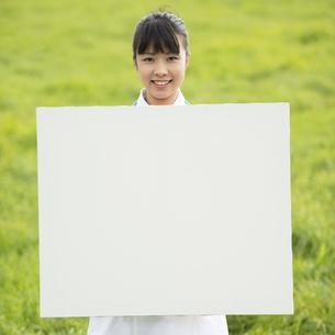 草原でホワイトボードを持つ看護師の写真素材 [FYI04558161]